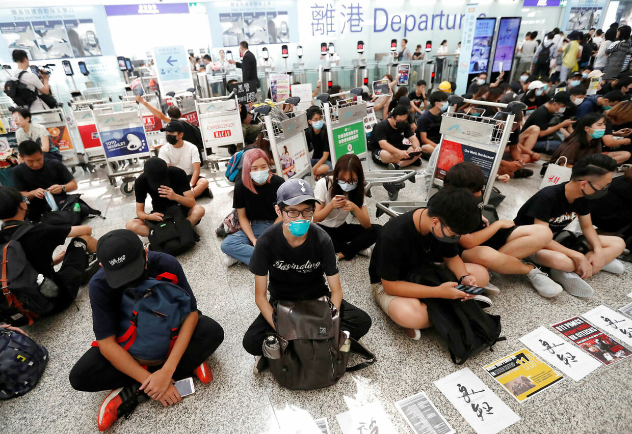 Anti-government protesters sit on the floor in front of security gates during a demonstration at Hong Kong Airport, China August 13, 2019. REUTERS/Issei Kato