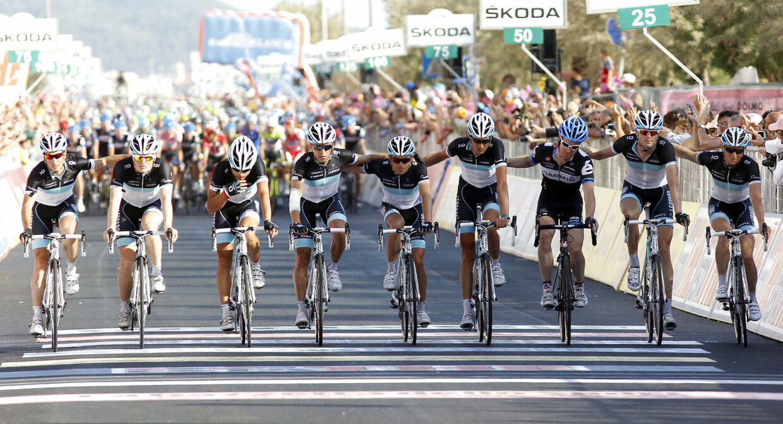 Hele Leopard-Trek-holdet krydser målstregen sammen ved fjerde etape af Giro d'Italia i 2011, efter Wouter Weylandts tragiske død.