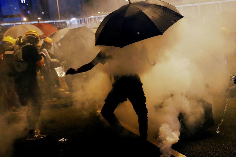 Demonstranterne bruger paraplyer til at beskytte sig mod tåregasen i Hong Kong.