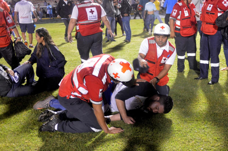 En tilskuer ligger i græsset og får hjælp af rednigsmandskab. Der blev smidt tåregas. Tre mennesker har mistet livet efter optøjerne.