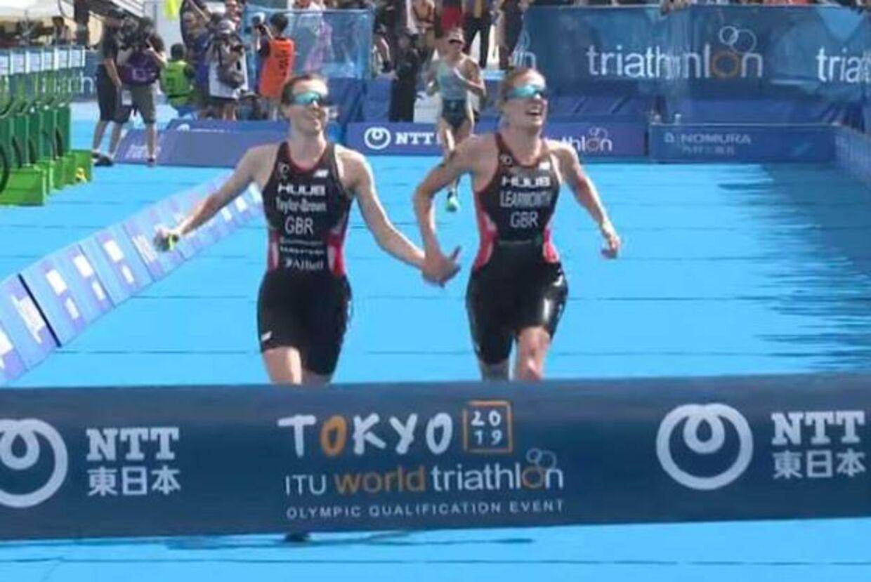 Jess Learmonth og Georgia Taylor-Brown løber over stregen hånd i hånd.
