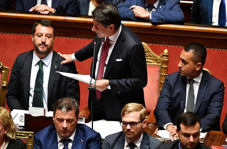 Italiens premierminister Giuseppe Conte, der står op på billedet, lægger en hånd på skulderen af Matteo Salvini, der er indenrigsminister.