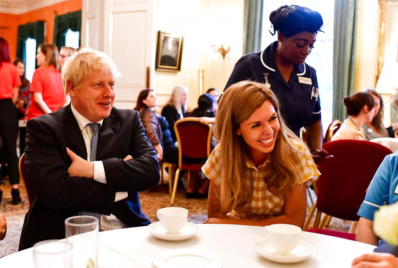 Premierminister Boris Johnson sidder ved siden af sin partner, Carrie Symonds, ved en komsammen for de ansatte i Downing Street nr. 10.