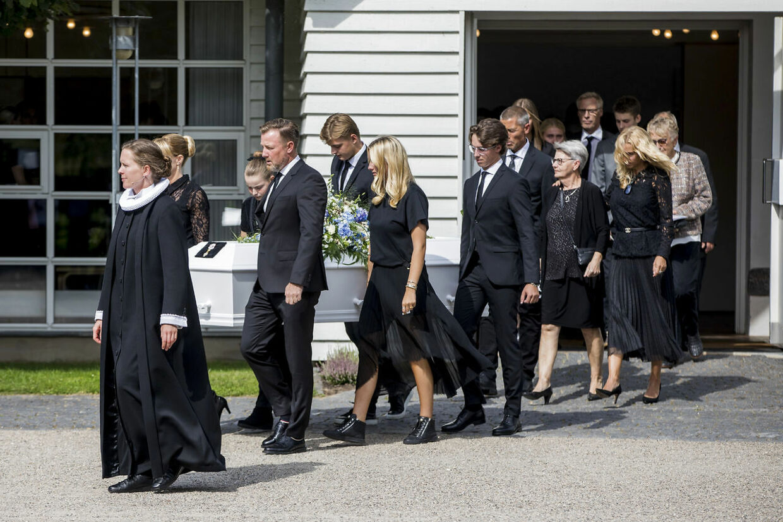 Kisten bæres ud. Forrest går Lars Larsens to børn, Mette Brunsborg og Jacob Brunsborg, og bag kisten går hans hustru, Kristine Brunsborg.