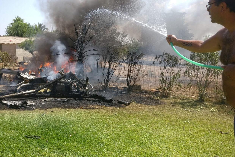 En mand pøser vand på vragdele, efter at en helikopter og et mindre fly stødte sammen i luften over Inca-området på den spanske ferieø Mallorca søndag. Handout/Reuters