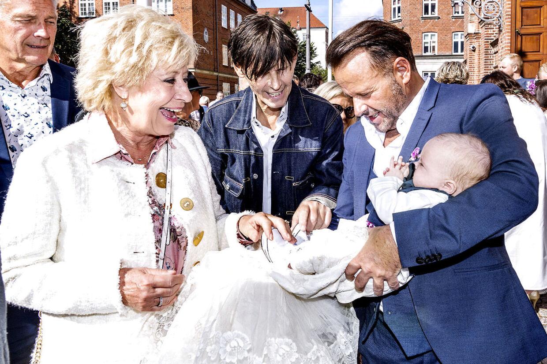 Birthe Kjær hilser på Lucas og Dennis Knudsen efter dåben.