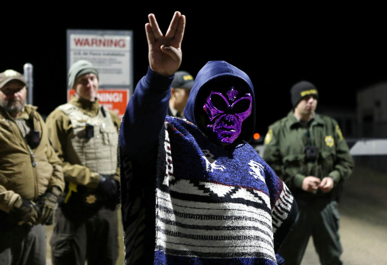 En mand iført alienmaske og poncho laver alien-hilsen ved porten til Area 51.
