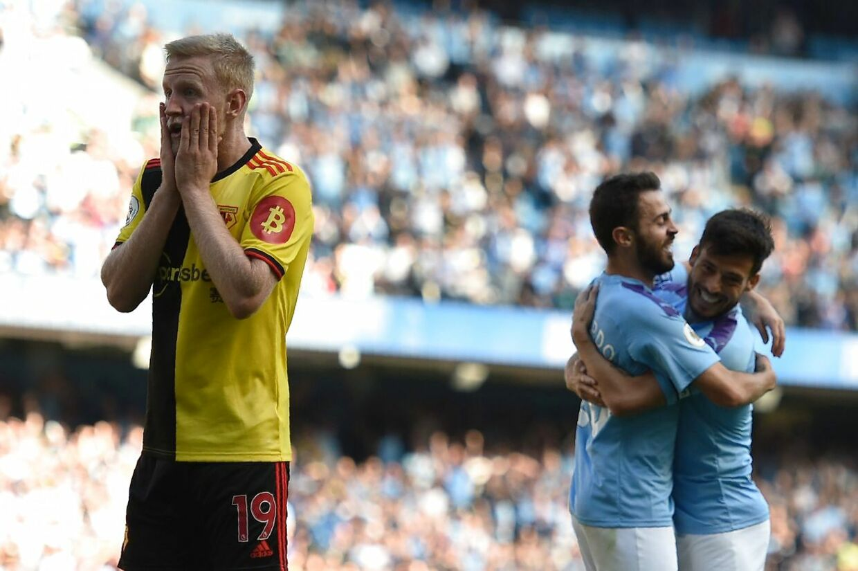 Watford's English midfielder Will Hughes reacts as Manchester City's Portuguese midfielder Bernardo Silva (CL) celebrates with Manchester City's Spanish midfielder David Silva after he scores the team's sixth goal during the English Premier League football match between Manchester City and Watford at the Etihad Stadium in Manchester, north west England, on September 21, 2019. (Photo by Oli SCARFF / AFP) / RESTRICTED TO EDITORIAL USE.No use with unauthorized audio, video, data, fixture lists, club/league logos or 'live' services. Online in-match use limited to 120 images. An additional 40 images may be used in extra time.No video emulation. Social media in-match use limited to 120 images. An additional 40 images may be used in extra time.No use in betting publications, games or single club/league/player publications. /