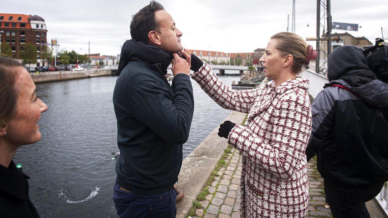 Statsminister Mette Frederiksen hjælper Irlands premierminister Leo Varadkar med en cykelhjelmen.
