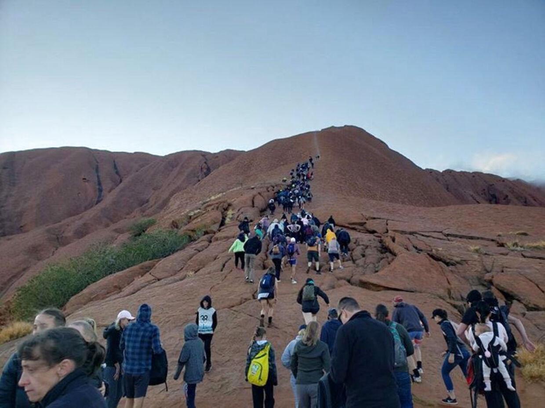 Turister kæmper sig vej mod toppen af Uluru den 25. september 2019.