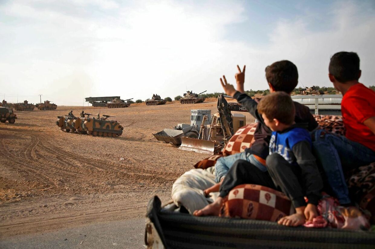 TOPSHOT - Syrian Arab civilians flash the victory sign as Turkish armoured personnel carriers and US-made M60 taks gather in the village of Qirata on the outskirts of the northern Syrian city of Manbij near the Turkish border, on October 14, 2019. - Turkey wants to create a roughly 30-kilometre (20-mile) buffer zone along its border to keep Kurdish forces at bay and also to send back some of the 3.6 million Syrian refugees it hosts. (Photo by Aaref WATAD / AFP)