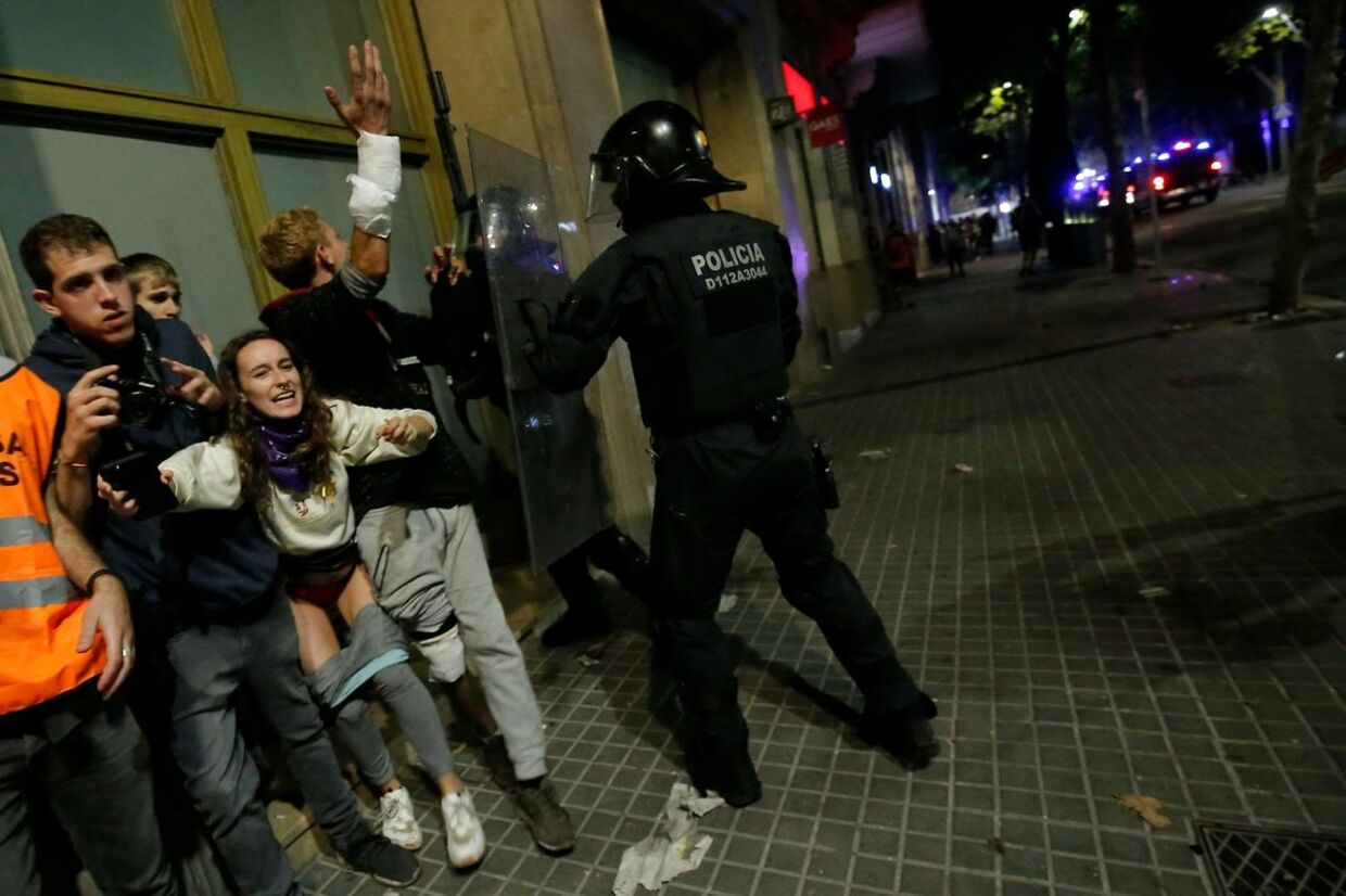 Protesters clash with a policeman in Barcelona, on October 18, 2019, after violence escalated during clashes, with radical separatists hurling projectiles at police, who responded with teargas and rubber bullets sparking scenes of chaos in the city centre. - The deterioration came after several hours of clashes on the fifth consecutive day of protests in the Catalan capital and elsewhere over Spain's move to convict nine separatist leaders of sedition over a failed independence bid two years ago. (Photo by Pau Barrena / AFP)