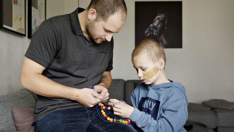 Magnus kigger sin supersnøre med sin far, Claus Funder Nielsen. Hver gang han har fået en behandling på sygehuset, får han en ny perle.