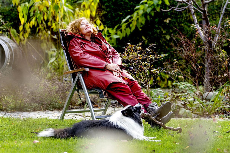 Sammen med hunden Andy nyder Lone Ciesla en efterårsdag i sin have.