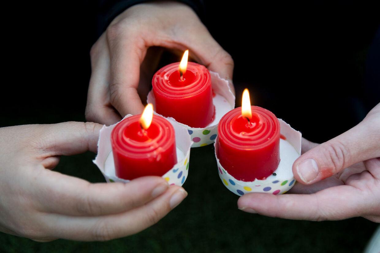 Tre kvinder holder lys ved en mindestund for Grace Millane.