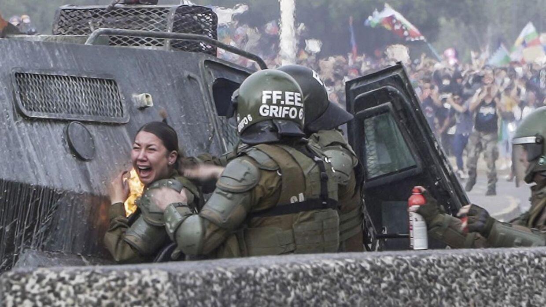 En kvindelige politibetjent bliver ramt af en molotov cocktail i forbindelse med demonstrationer i Santiago i Chile.