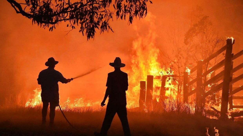 Her ses to borgere, der beskytter deres ejendom mod flammerne i Australien.