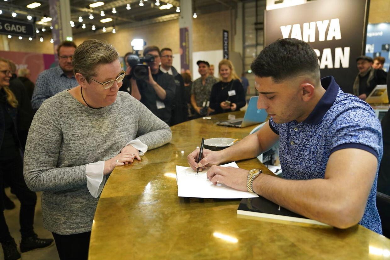 Folk står i land kø for at få signeret en bog. Yahya når dog ikke alle, før han bliver træt og må gå.