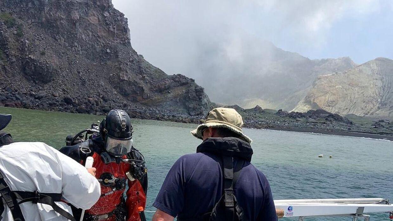 Dykkere gør sig klar til at springe i vandet ud for White Island for at lede efter omkomne for vulkanudbruddet.