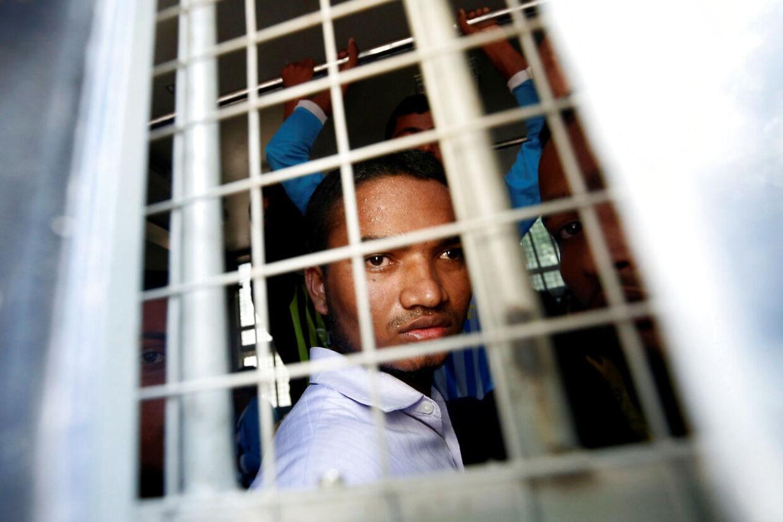 En muslimsk mand fra Rohingya-stammen ser ud fra en polititransportbil.