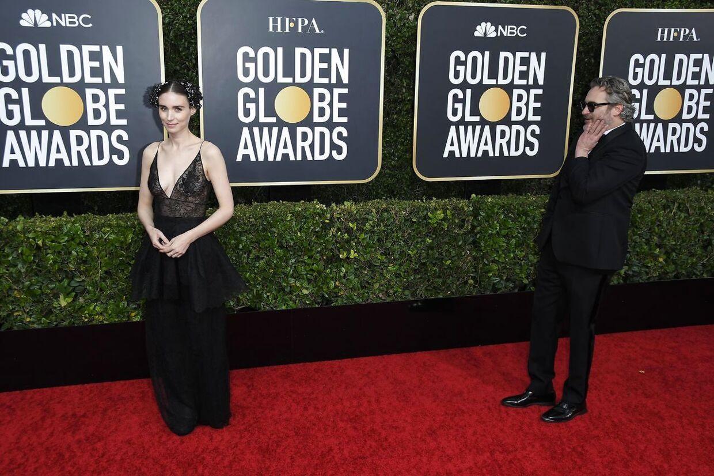 Her ses Joaquin Phoenix kigge beundrende på sin kæreste, Rooney Mara.