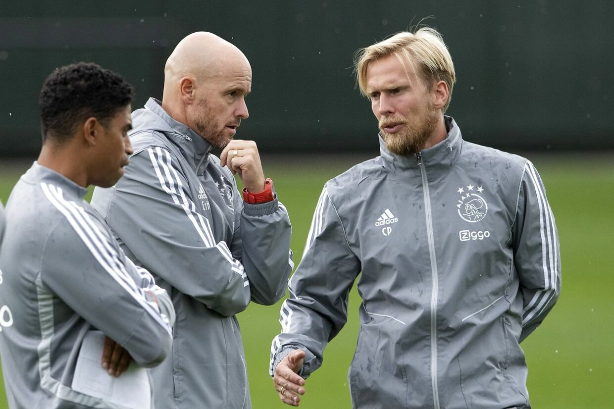 Trainer Erik ten Hag (C) speaks with his assistants Michael Reiziger (L) and Christian Poulsen during a training of Ajax Amsterdam, on August 12, 2019 in Amsterdam. Ajax will play on August 13, 2019 against PAOK Saloniki in the third preliminary round of the UEFA Champions League Olaf Kraak / ANP / AFP