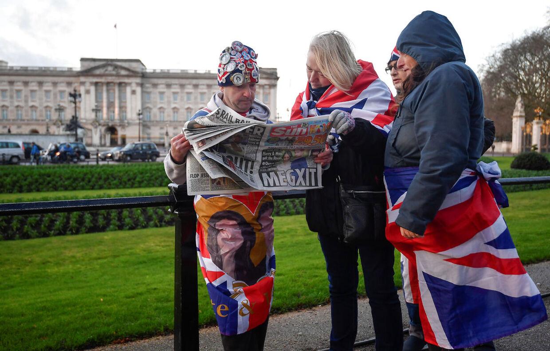 En gruppe royalister har taget opstilling foran Buckingham Palace i London, hvor den royale sag kaldes 'Megxit' på forsiden af aviserne.