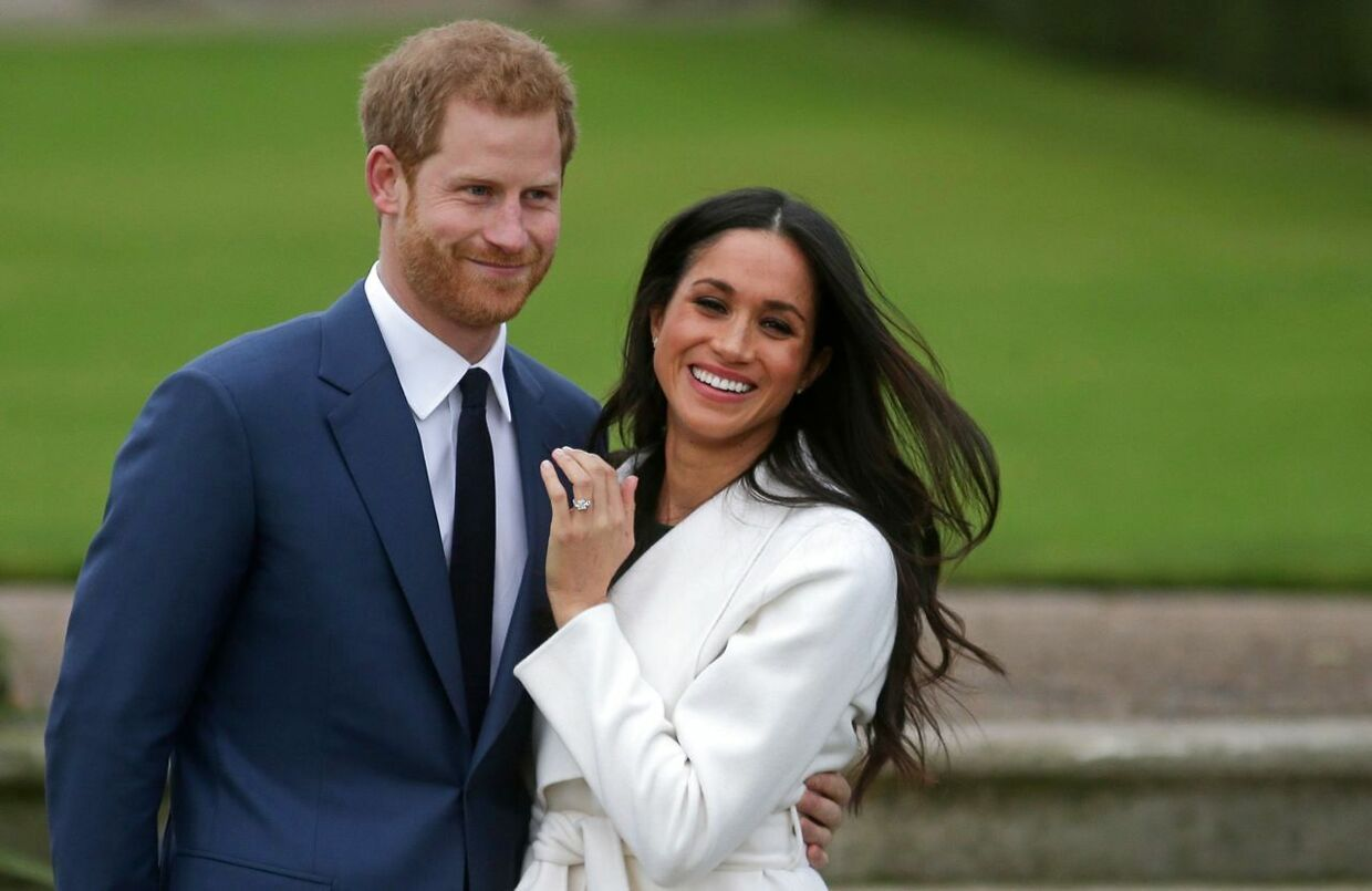 (FILES) In this file photo Britain's Prince Harry stands with his fiancée US actress Meghan Markle as she shows off her engagement ring whilst they pose for a photograph in the Sunken Garden at Kensington Palace in west London on November 27, 2017, following the announcement of their engagement. - Queen Elizabeth II and other senior British royals were gathering for a meeting Monday with Prince Harry in an attempt to solve the crisis triggered by his bombshell announcement that he and wife Meghan were stepping back from the royal frontline. Harry's father Prince Charles and brother Prince William, with whom he has strained relations, will join the monarch at her private Sandringham estate in eastern England, according to British media. (Photo by Daniel LEAL-OLIVAS / AFP)