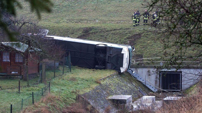 Et redningsteam arbejder på ulykkesstedet, hvor en skolebus er forulykket. To børn er dræbt og 20 såret.