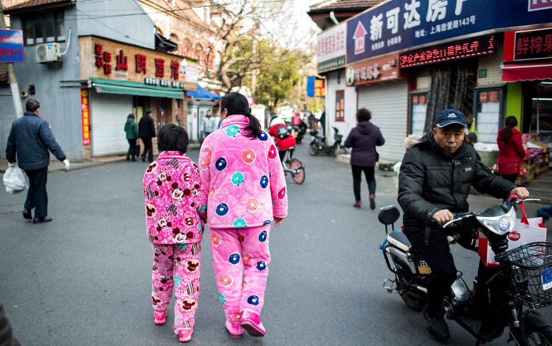 En kvinde går offentligt rundt på en gade i Shanghai iført pyjamas.