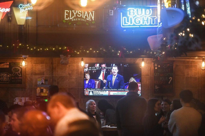 På tv i denne bar i New York kører rigsretssagen også.
