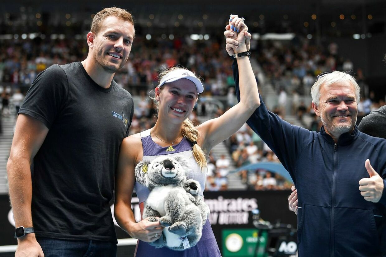 (L-R) David Lee, husband of Denmark's Caroline Wozniacki and her father Piotr Wozniacki celebrate after her defeat against Tunisia's Ons Jabeur their women's singles match on day five of the Australian Open tennis tournament in Melbourne on January 24, 2020. (Photo by Greg Wood / AFP) / IMAGE RESTRICTED TO EDITORIAL USE - STRICTLY NO COMMERCIAL USE