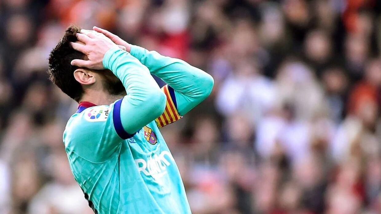 Lionel Messi tager sig til hovedet i kampen mod Valencia, der havde en frygtelig optakt med slagsmål mellem to af holdenes fangrupperinger.