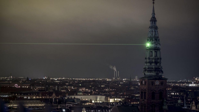 En grøn laserstråle lyser op i København.