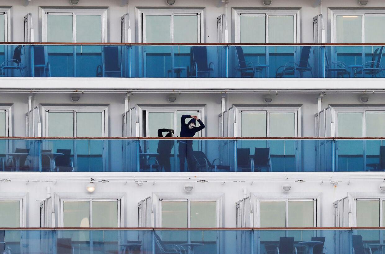 En passager i en kahyt med balkon trækker lidt frisk luft midt i sin 14 dages karantæne.