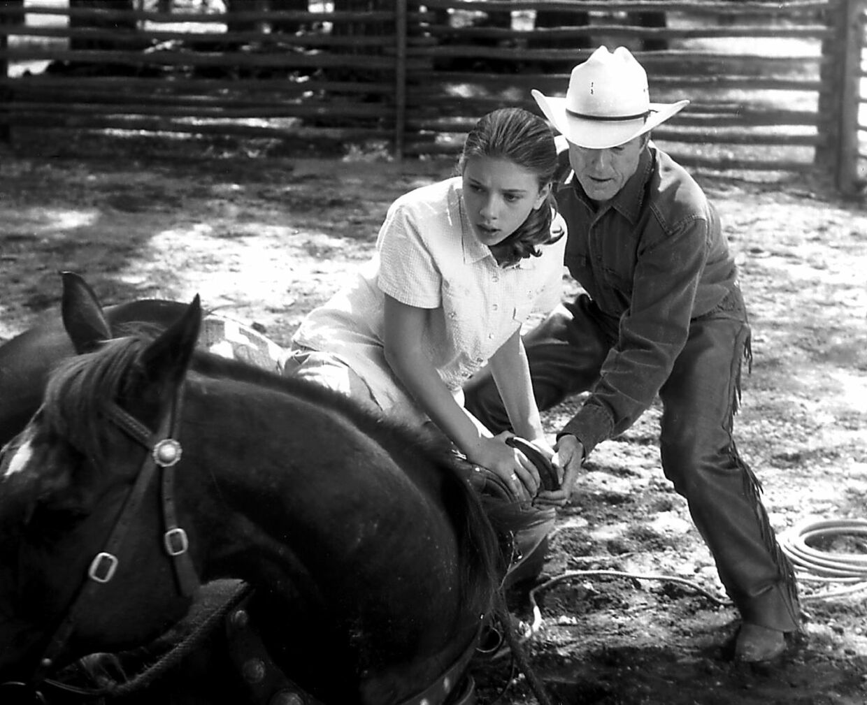 """In an emotional scene from the movie """"The Horse Whisperer, """" actress Scarlett Johansson (L), is helped into the saddle by actor Robert Redford after being traumatized in a horseback riding accident. The movie is based on the best-selling book """"The Horse Whisperer"""" by Nicholas Evans who regularly consulted with renowned horse trainer Monty Roberts. (B/W) AFP PHOTO/Elliott MARKS/TOUCHSTONE PICTURES"""