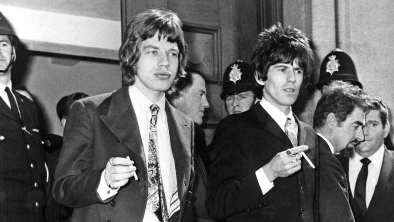 Mick Jagger og Keith Richards for sig en smøg foran retsbygningen i Chichester 11. maj 1967. Der var i retten på grund af en tiltale for ulovlig besiddelse af narkotika.