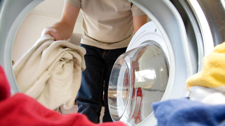 Mand der vasker tøj i en vaskemaskine.