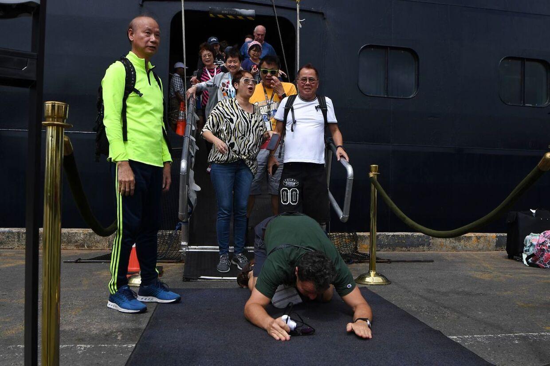 En passager kaster sig til jorden, da passagererne endelig får fast grund under fødderne i Cambodia. (Photo by TANG CHHIN Sothy / AFP)