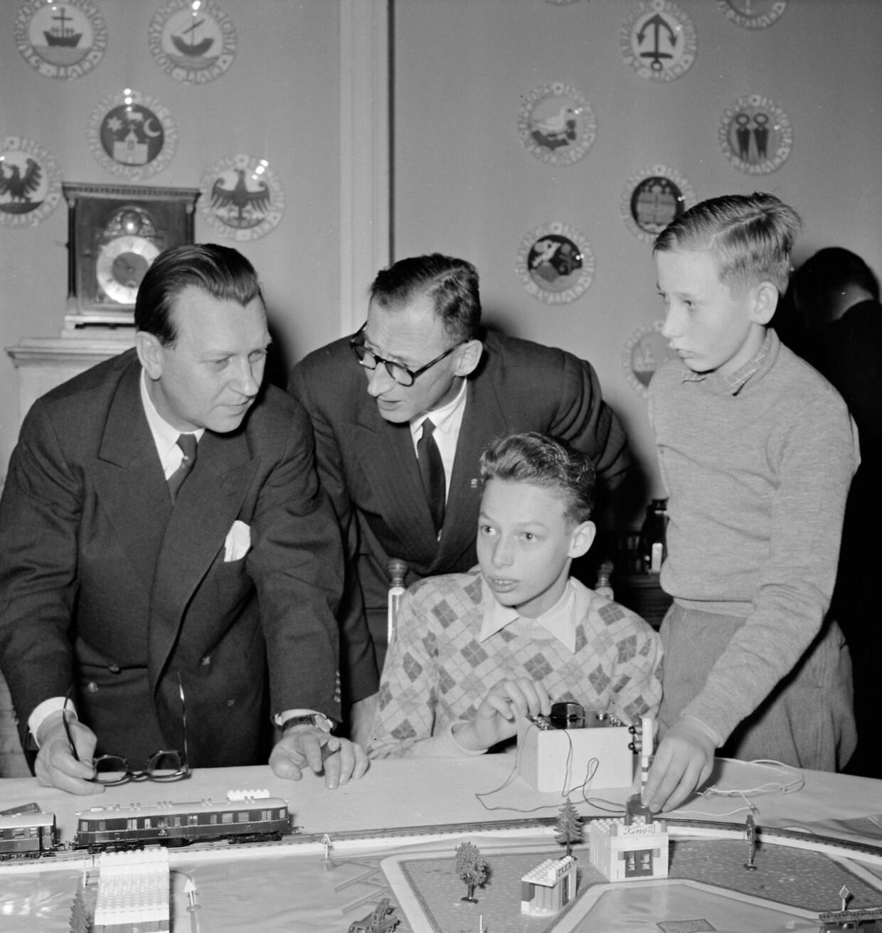 Modeltog har altid været et hit for drenge – tilsyneladende også for prins Ingolf og hans lillebror, prins Christian. De ses her sammen med statsminister H.C. Hansen samt deres far, arveprins Knud.