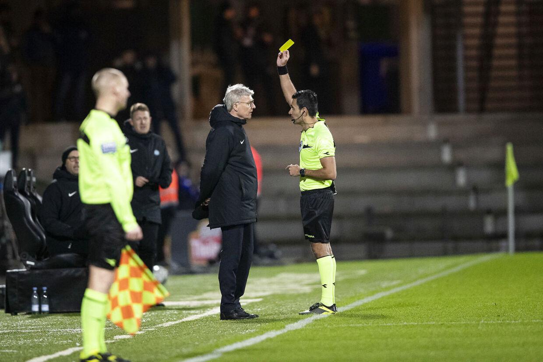 Esbjerg-træner Lars Olsen får en advarsel af dommer Sandi Putros under fredag aftens Superligakamp mellem Esbjerg fB og FC København.