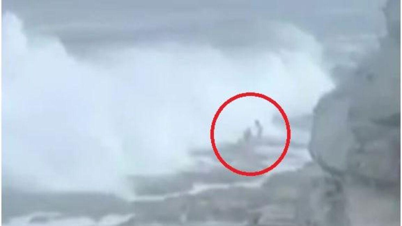Stilbillede fra videoen taget af Sayed Kazem, hvor man ser den store bølge skylle Andrei og Yulia ud i havet ved Bondei Beach, Australien.