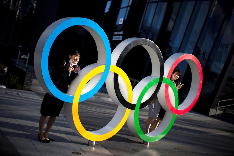I Tokyo er man ved at være i OL-stemning. Her poserer en japaner ved OL-ringene, der er stillet op ved Japan Olympic Museum.