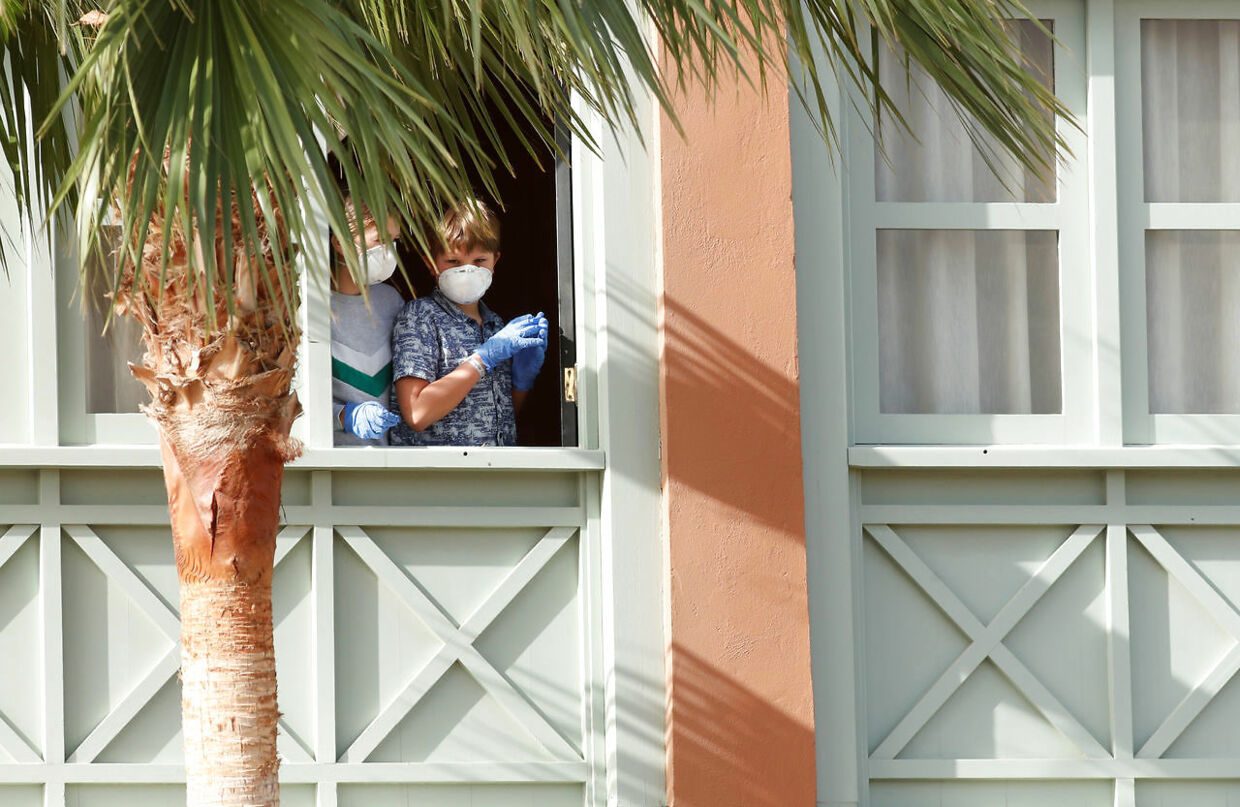 Guests, wearing protective face masks, look out from a window at H10 Costa Adeje Palace, which is on lockdown after cases of coronavirus have been detected there in Adeje, on the Spanish island of Tenerife, Spain, February 26, 2020. REUTERS/Borja Suarez
