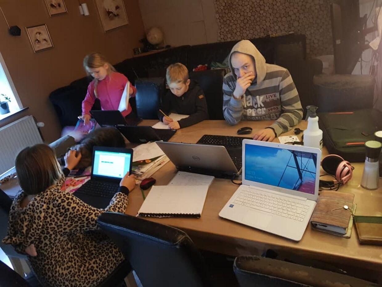 De tre skolebørn og deres far samlet om spisebordet, mens børnene laver skoleopgaver og far prøver at koncentrere sig om arbejde