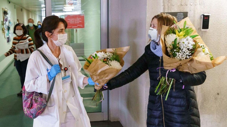 En blomsterhandler giver blomster til sundhedsmedarbejdere foran et hospital i den nordspanske by Burgos. Mere end 5.400 spanske sundhedsmedarbejdere er testet positive for coronavirus.