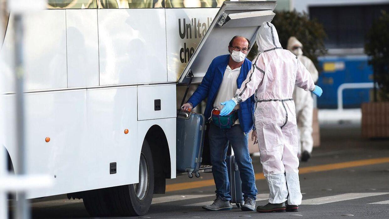 En passager fra krydstogtsskibet Costa Luminosa kommer på en bus efter evakueringen i den italienske havneby Savona.