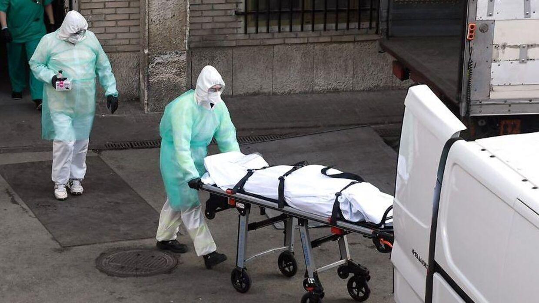 En sundhedsarbejder kører en afdød patient væk fra et hospital i Madrid. Spanien har nu registreret flere corona-relaterede dødsfald end Kina.