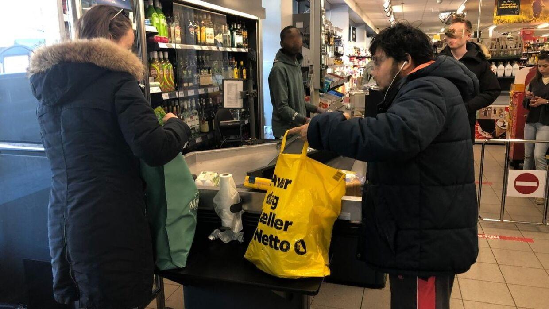 To personer i Netto står, og pakker deres varer ned.