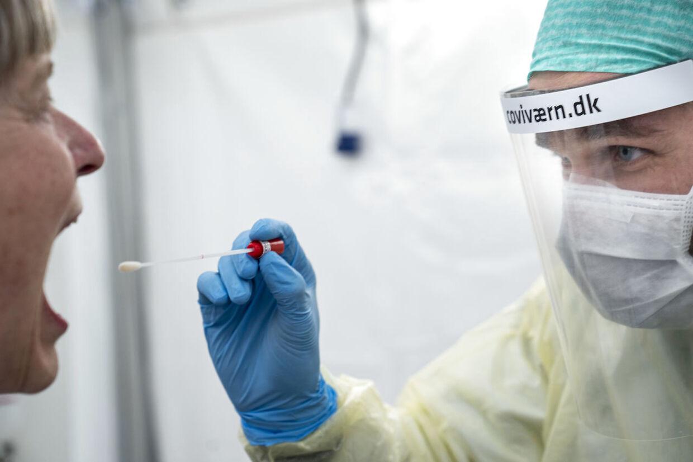Læge ifører sig værnemidler og demonstrerer en podning i det nye podetelt på Rigshospitalet i København, torsdag den 2. april 2020. Teltet skal øge hospitalets podningskapacitet og er ved at blive indrettet til at tage imod endnu flere patienter til podning for coronavirus. (Foto: Niels Christian Vilmann/Ritzau Scanpix)